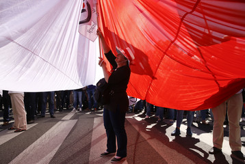 A woman stands under a giant Polish flag during anti-government demonstration organized by main opposition parties in Warsaw