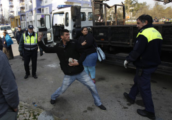 Mateus Silva, 25 and unemployed, throws stones at his caravan while city police officers arrive to evict him in the Nossa Senhora de Fatima neighborhood