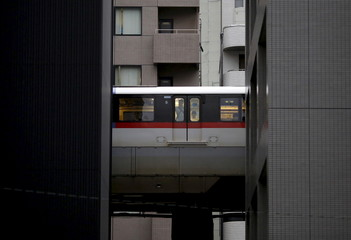 A man looks through window of monorail as it travels past office buildings in Tokyo