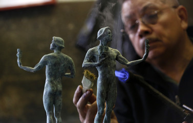 """Worker Quintero applies a patina on """"The Actor"""" statuette during a media event on the production of the statuettes for the 20th annual Screen Actors Guild Awards at American Fine Arts Foundry in Burbank"""