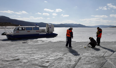 Members of the Rescuer state regional service talk to a fisherman to convince him to leave the thin ice during a daily patrol raid along the frozen Yenisei river