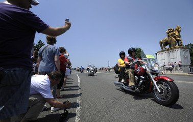 People watch motorcycle riders take part in the 25th annual Rolling Thunder First Amendment Demonstration Run in Washington