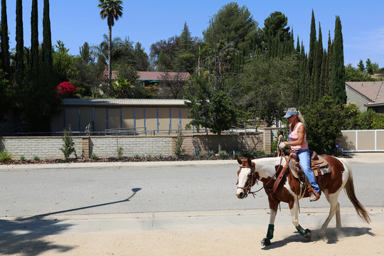 A rider passes the barns behind the house where Rae Greulich and her husband Dan, who died from an antibiotic resistant infection, once lived in Simi Valley
