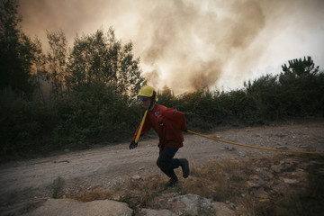 A firefighter runs to extinguish a forest fire near Mengualde