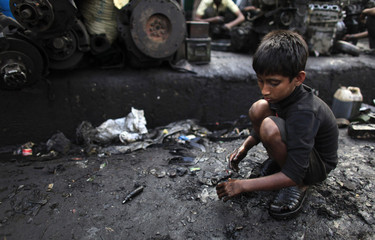 Masud, 6, collects scraps near a vehicle spare parts store in Dholaikhal
