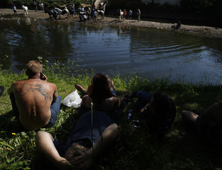A Member of the traveller community with a horse themed tattoo watches as people wash their horses in the river Eden during the horse fair in Appleby-in-Westmorland, northern Britain.
