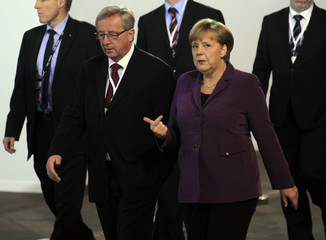 Eurogroup Chairman Juncker walks with German Chancellor Merkel as they at the G20 venue where world leaders gather in Cannes
