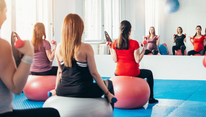 Group of pregnant women exercising and lifting weights from the back