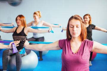 Beautiful pregnant women enjoying exercise during Pilates class stretching