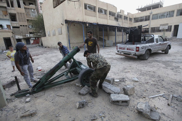 Free Syrian Army fighters prepare to launch a rocket against forces loyal Syria's President al-Assad in Deir al-Zor