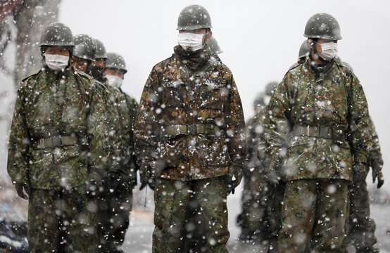 Japan Self-Defense Force officers arrive at the devastated residential area of the tsunami hit Otsuchi as heavy snow falls