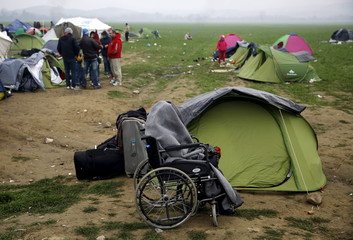 A temporarily stranded Syrian refugee is seen on a wheelchair on a field at a makeshift camp next to the Greek-Macedonian border, near the Greek village of Idomeni