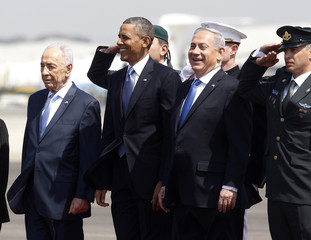 U.S. President Obama stands in between Israeli PM Netanyahu and President Peres upon his arrival at Ben Gurion International Airport in Tel Aviv