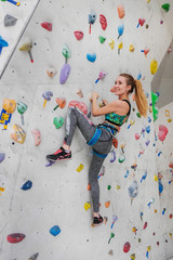 Woman climbing on climbing wall. Teenage rock climber.