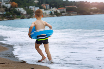 Cute little boy with colorful rubber ring on summer beach