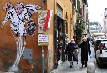 A priest and a nun walk by a large drawing  of Pope Francis depicting him as a superhero on a wall near the Vatican