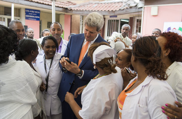 U.S Secretary of State John Kerry looks at a cellphone as he is surrounded by healthcare workers during a visit to the Gandhi Memorial Hospital in Addis Ababa