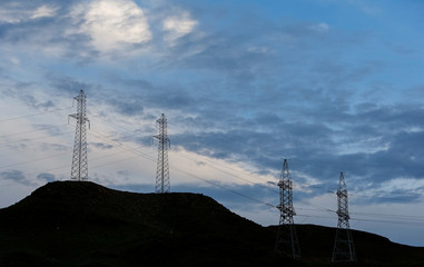 Electrical power pylons of high-tension electricity power lines are silhouetted against cloudy sky outside Almaty