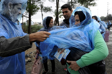A migrant man covers a woman with a plastic raincoat to protect from rainfall as they wait to cross Greece's border with Macedonia near the Greek village of Idomeni