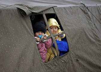 Children look out from a tent at a migrant camp in Opatovac