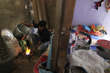 Ceopa lights a fire to cook popcorn at his home to sell in the shantytown of Pamplona Alta in Lima