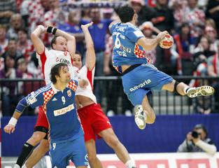 Croatia's Lackovic attempts to score next to Denmark's Jorgensen and Mogensen during their Men's European Handball Federation Championship second round match in Vienna