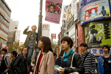 A boy stands on a post to take pictures of Shibuya junction, which is popular among tourists, in Tokyo