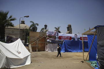 A member of Muslim Brotherhood and supporter of deposed President Mursi walks near tents in front of main gate of Cairo University in Giza