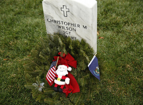 A Santa and the state flag of Maine are placed by a grave in Arlington National Cemetery's Section 60 in Virginia