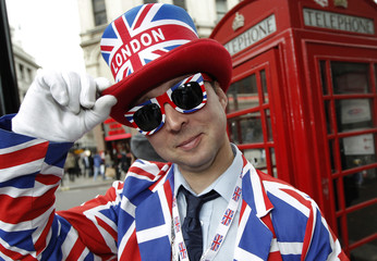 Man dressed in a suit and hat with Union Jack flag design poses in Picadilly Circus in London