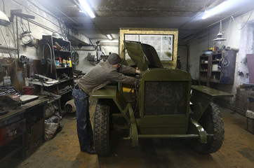 Worker repairs Soviet-era ZIS-5 truck from collection of Tsitovich, who finds and restores old cars and motorcycles, at his base in Zabroddzie