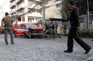 Policemen inspect a taxi damaged in an explosion in Ekamai area in central Bangkok