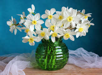 Bouquet of white daffodils in a green vase.