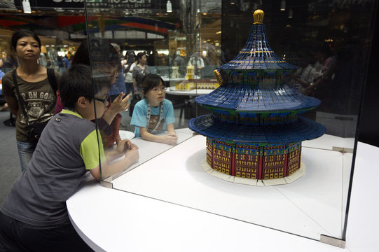 Visitors look at a miniature model of Chinese The Temple of Heaven, which was made from 100,000 pieces of Lego blocks, during LEGO Piece of Peace-World Heritage Exhibition in Hong Kong