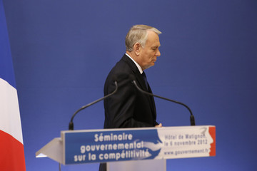 French Prime Minister Ayrault leaves after a news conference to outline the Socialist government's plans for restoring industrial competitiveness at the Hotel Matignon offices in Paris