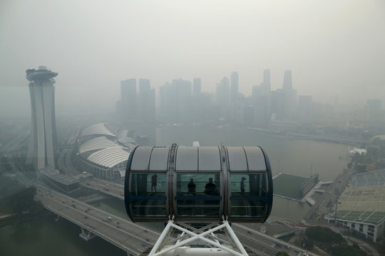 Tourists sit in a capsule on the Singapore flyer observatory wheel overlooking the skyline of the central business shrouded by haze in Singapore