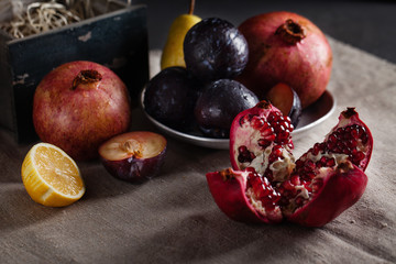 Pomegranate, plum, pear, lemon on the table