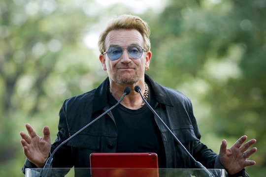 Irish singer Bono speaks to the guests before the unveiling of a tapestry honoring John Lennon at Ellis Island in New York