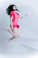 Happy brunette woman jump and have fun on a white backaround