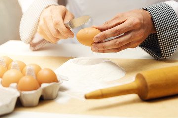 chef cracking egg with knife over flour heap