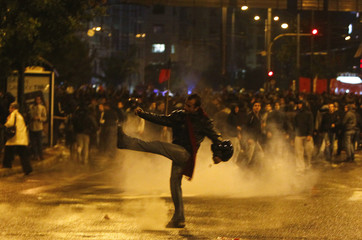 A protester kicks a teargas canister outside the U.S embassy during a rally in Athens