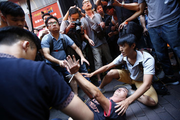 A man, who a witness said started a fight with several pro-democracy protesters, lies on the ground with hands tied by the protesters near a barricade on a main street in Hong Kong's Mongkok shopping district