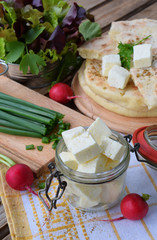 Square cubes of traditional greek cheese feta with flat bread, lettuce, onion and radish on wooden background.