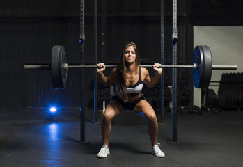 Beautiful female brunette athlete squatting with heavy weights wearing shorts and sports bra showing her six pack abs