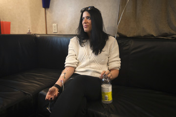 Meredith Koko sits and watches TV as she receives a vitamin infusion via intravenous drip on the Hangover Bus in the Manhattan borough of New York