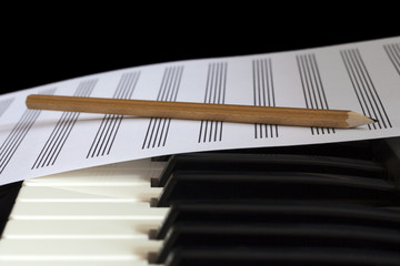 Piano keyboard and empty musical sheet with pencil, close-up