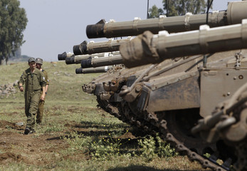 Israeli soldiers walk near tanks close to the ceasefire line between Israel and Syria on the Israeli occupied Golan Height