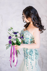 beautiful sexy Oriental girl with makeup black curls in a bright green sequined dress with purple and pink bouquet on his hand looking down profile on white gray background