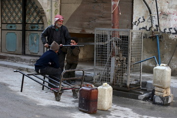 Residents push a lever to fill water containers in Douma, Syria
