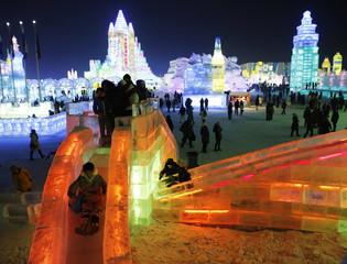 A visitor rides a slide on an ice sculpture during a light-up rehearsal ahead of the Harbin Ice and Snow Sculpture Festival in Harbin